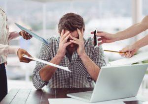 Homme se tient la tête à cause du stress